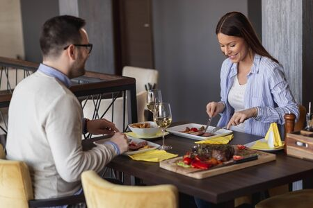 Photo pour Couple in love on a date, having dinner at a restaurant, drinking wine and having a nice time together - image libre de droit