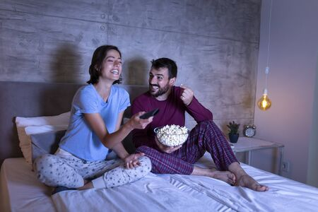 Foto de Couple in love lying in bed, eating popcorn and watching a movie, relaxing at home at night - Imagen libre de derechos