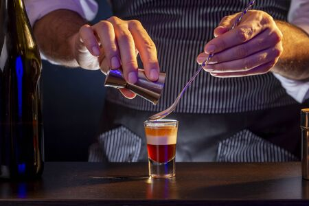 Photo pour Bartender making B-52 layered cocktail, pouring irish cream from a measuring cup into a shot glass using cocktail spoon - image libre de droit