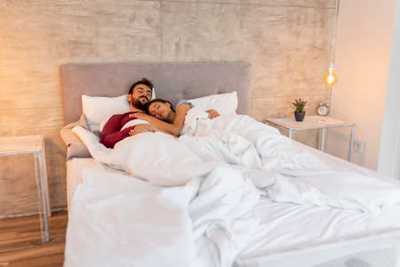 Photo pour Beautiful young couple in love lying in bed after waking up in the morning, laughing, hugging and enjoying time together - image libre de droit