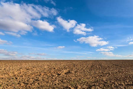Photo pour Plowed agricultural farm field pattern and perfect sky - image libre de droit