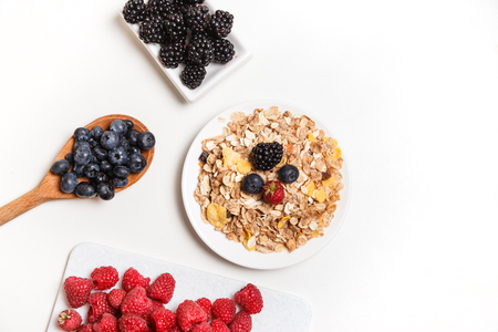 bowl of corn flakes with berries on white background