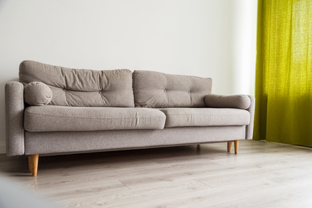 Photo pour Grey sofa in monochromatic living room with green curtains - image libre de droit