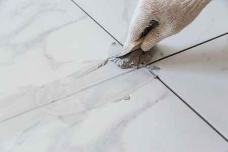 Photo pour Grouting tiles seams with a rubber trowel. - image libre de droit