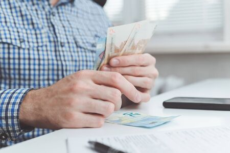 Photo pour Businessman calculates the costs incurred or salary. - image libre de droit