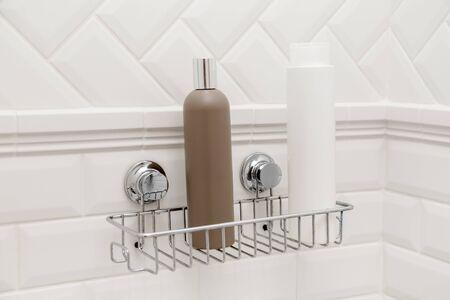 Photo pour Toiletries bottles on suction cups compact bath shelf, fixing on tiled wall without drilling. - image libre de droit