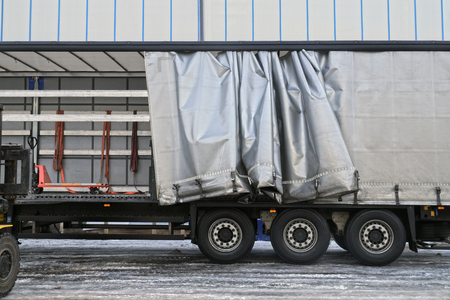 Photo pour Transport and unloading. A semi-trailer with an exposed tarpaulin during unloading. - image libre de droit