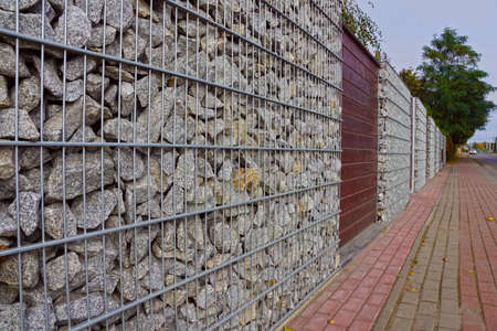 Photo for Gabions. A fragment of a fence made of gabions. Separation of the street from residential areas. - Royalty Free Image