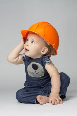 Photo pour Boy wearing hard hat playing with building blocks toy - image libre de droit