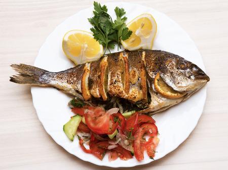Foto de Cooked fish sea bream fish with lemon, parsley,garlic  - Imagen libre de derechos