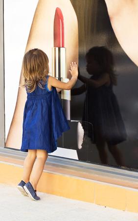 Little girl looking through shop window
