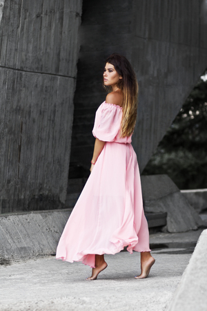 Young woman in pink dress walking. Soft colors.