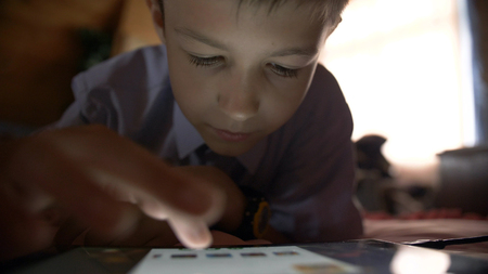 Photo pour boy lays in a bed and touches on a tablet PC at home - image libre de droit