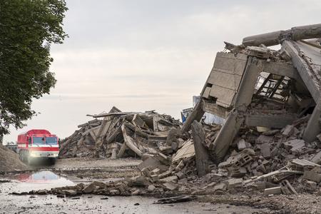 Photo pour Fire brigade car among collapsed concrete buildings - image libre de droit