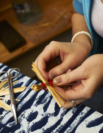 Detail of hands creating a straw Christmas decoration.