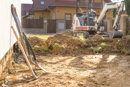 Photo pour Mini excavator on construction site. Excavator regulates the terrain around the house. Digger digging soil with shovels in foreground - image libre de droit