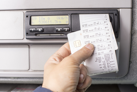 Photo pour Digital tachograph and drivers hand holding print with driving times of the day - image libre de droit