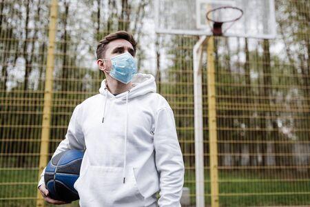 Foto de A man in a mask on a playground with a basketball ball - Imagen libre de derechos