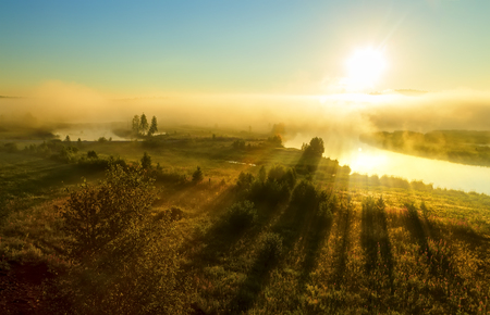 Beautiful sunrise flight sun over misty river (foggy morning). Summer fog and sun on peaceful river. Holiday destination, place for rest, meditative state