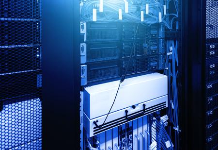 Photo pour Severs computer in rack at large data center under blue neon light. Network and technology futuristic concept - image libre de droit