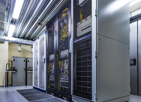 Photo pour Room with server rack of hardware, cloud storage in big data center. Technical equipment and supercomputers with connected wires and cables in cabinets under closed grid door - image libre de droit