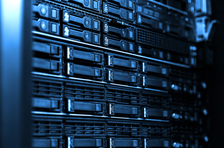 Photo pour Close up blade server equipment rack and storage in big data center. Technological background with blurred side frame cold blue tone - image libre de droit