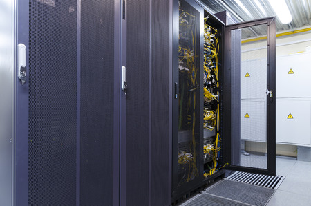 Big datacenter with connected servers and internet cable infrastructure in room. Fiber optic technology equipment with media converters and optical cables connected to rack with opened door