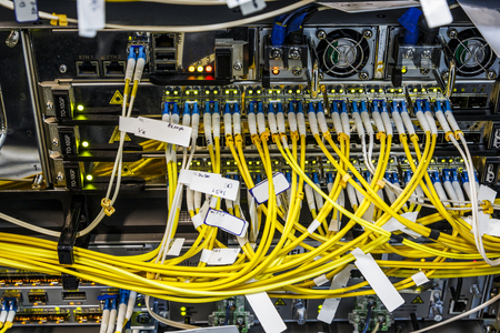 Photo pour Fiber optic wires cables connecting on core network swtich operations center. Server hardware in big data center. Part of rack mounted cabinet. Close up - image libre de droit