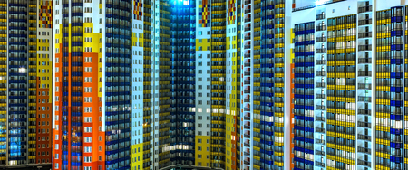 facade of residential apartments in a modern metropolis. Night, background texture