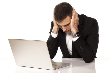 desperate young businessman leaning on both hands behind his laptop