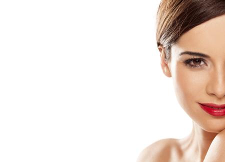 Photo pour half face of a beautiful young smiling woman on white background - image libre de droit