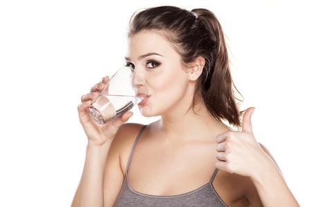 Foto de beautiful woman drinks water from a glass and showing thumb up - Imagen libre de derechos
