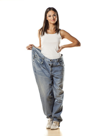 Photo pour happy pretty attractive girl posing in big size pants on a white background - image libre de droit