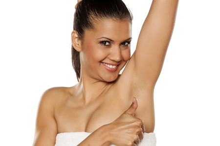 smiling young ethnic woman showing her shaved armpit and showing thumb up