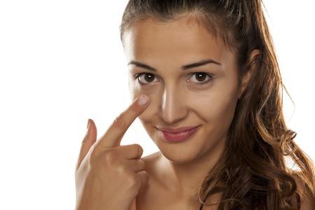 Photo pour young woman applied concealer on her eye circles - image libre de droit
