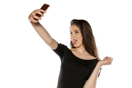 Foto de A young girl with long hair take selfies on a white background - Imagen libre de derechos