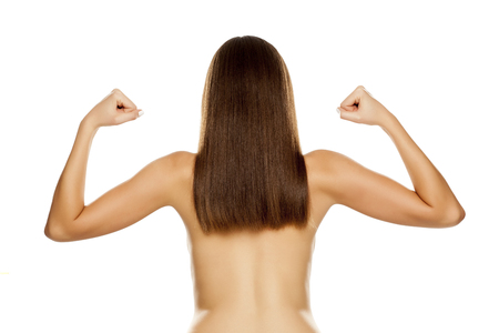 Foto de Back view of young nude woman with straight long hair, showing biceps on white background - Imagen libre de derechos