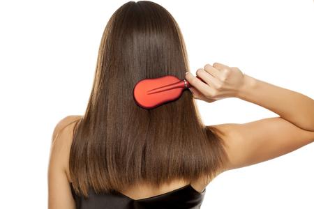 Foto de Back view of young woman combing her long hair on white background - Imagen libre de derechos