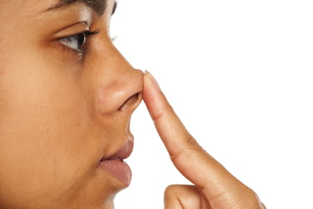 Photo pour Young dark skinned woman touching her nose - image libre de droit