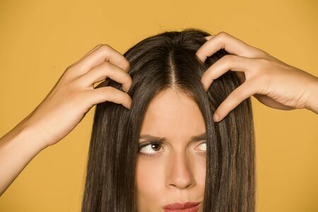 Photo pour Beautiful young woman with itchy scalp on yellow background - image libre de droit