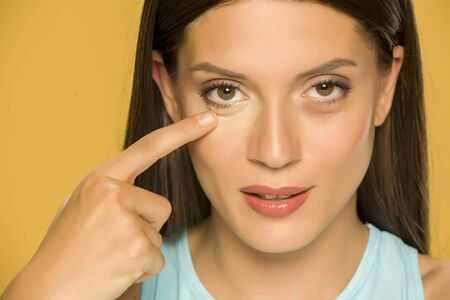Photo pour Young woman touching her low eyelids on yellow background - image libre de droit