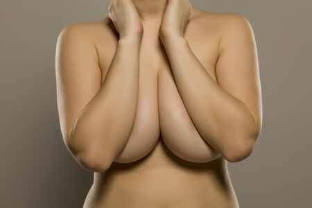 Photo pour Woman covering her big breasts with her hands on gray background - image libre de droit