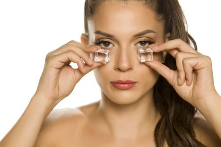 Photo pour young beautiful woman holding ice cubes under the eyes on white background - image libre de droit