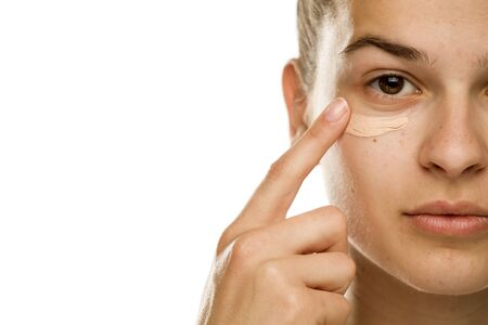 Photo pour Portrait of young woman applying concealer with her finger on white background - image libre de droit