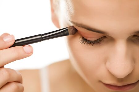 Photo pour Young woman applying a eyeshadow with brush - image libre de droit