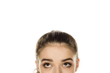 Photo for Young confused woman looking up on white background - Royalty Free Image
