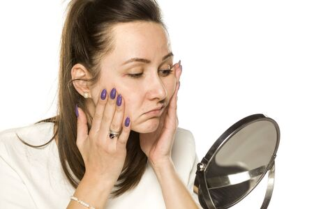 Photo pour bored woman looking at herself in the mirror on white background - image libre de droit