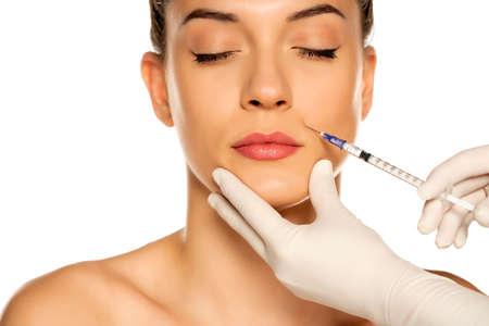 Photo pour Portrait of a young beautiful woman on a face filler injection procedure on white background - image libre de droit
