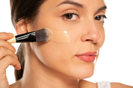 Photo for Young woman applying liquid foundation with the brush on her face - Royalty Free Image