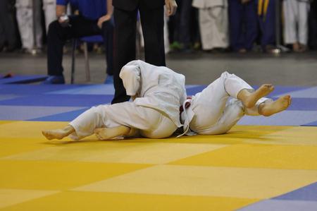 Two boys judoka in kimono compete on the tatami